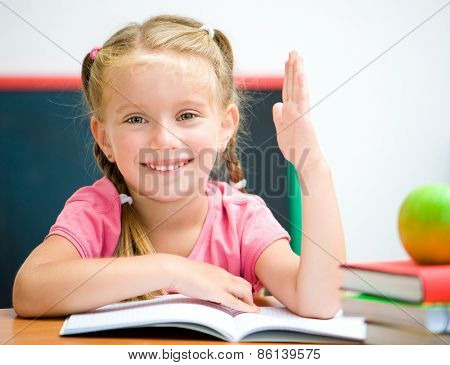 beautiful little girl at the desk raised her hand