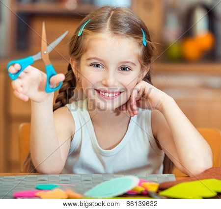 happy  little girl is engaged in needlework at home