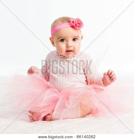 six-month girl in a pink skirt on a white background