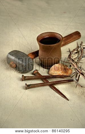 Crown of thorns, nails and mallet with communion elements over vintage cloth