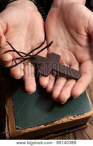 Closeup Of Hands Holding Vintage Cross On Bible