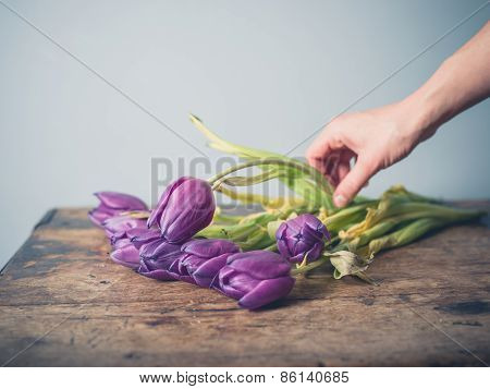 Hand Picking Up Dead Flowers From Table