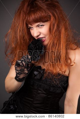 Gothic Redhead Woman In Sexy Black Satin Corset Against Dark Grey Background
