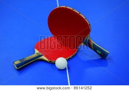 red racket and a ping pong on the table