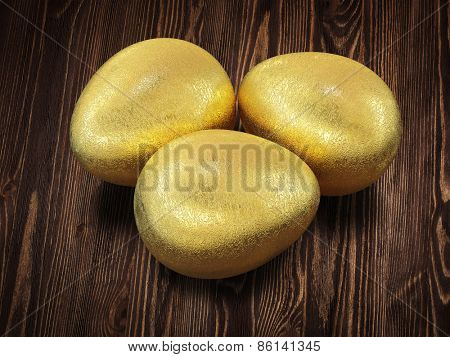 Three golden Easter eggs isolated on wooden background