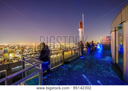OSAKA, JAPN - NOVEMBER 24, 2012: Tourists enjoy the skyline view from the Floating Garden Observatory on the Umeda Sky Building at night.
