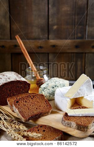 Brie Cheese, Bread Slices, Roquefort And Honey On A Board