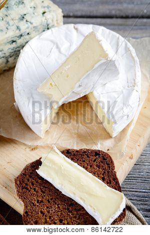 Camembert, Roquefort And Rye Bread Slice On A Cutting Board