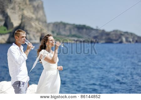 Couple Drinking Champagne In Wedding Day Near Sea Of Naples, Italy