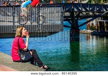 Woman in red blouse eating red ice cream