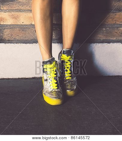 Girl Standing In Fashionable Sneakers Brick Wall. Urban Fashion Style