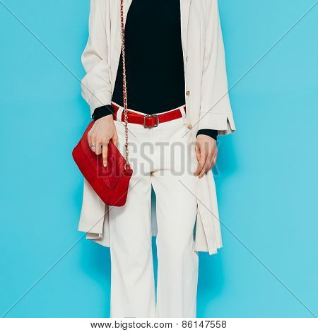 Fashion Lady In Stylish White Clothes. White Trousers And Raincoat With Red Accessories