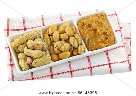 A dish of roasted groundnuts, salted peanuts and peanut butter, isolated on white