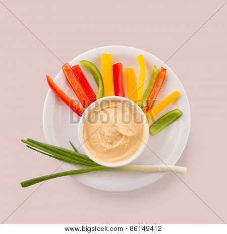 Hummus with capsicum and green onion over circular plate on pink background