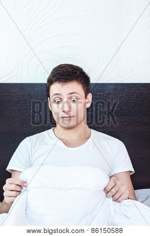 Good Looking Young Man In Bed Looking Down At His Penis Under White Covers