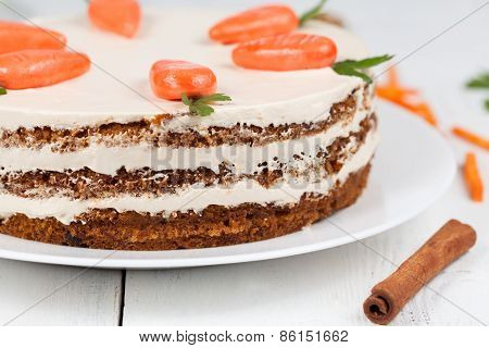 Tasty easter carrot cake with cream and little carrots on white plate