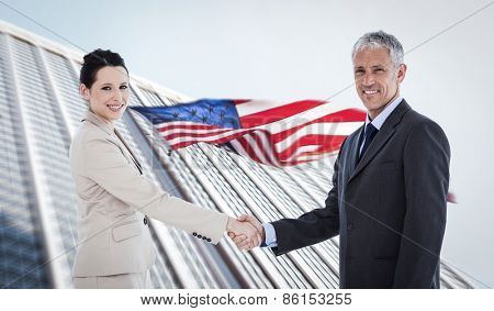Smiling business people shaking hands while looking at the camera against american flag and skyscraper
