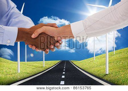 Close-up shot of a handshake in office against road leading out to the horizon with wind turbines either side