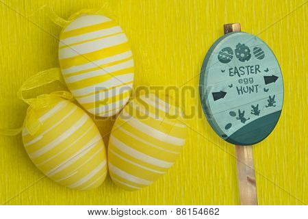 Easter egg hunt sign against three easter eggs