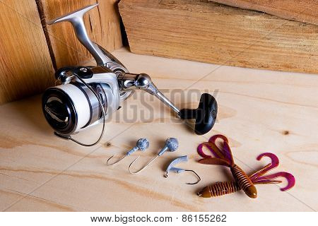 Fishing Reel With Silicone Baits On Wooden Background.