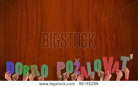 Hands holding up dobro pozalovat against wooden oak table