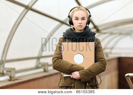 Young beautiful hipster woman in big dj headphones posing with a vinyl records on subway entrance