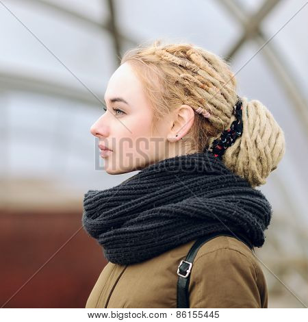 Closeup portrait of young beautiful blonde woman with a dreadlocks bun hairstyle