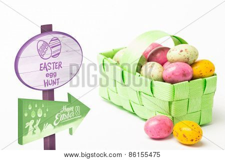 Easter egg hunt sign against colourful easter eggs in a green wicker basket