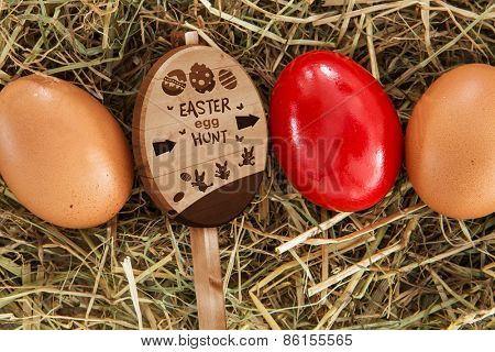 Easter egg hunt sign against red egg on straw with plain ones