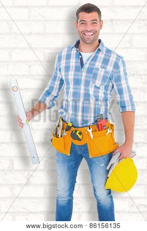 Portrait of smiling manual worker holding spirit level against white wall
