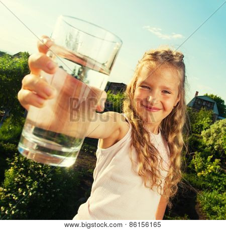 Girl holding glass with water. Happy child at summer