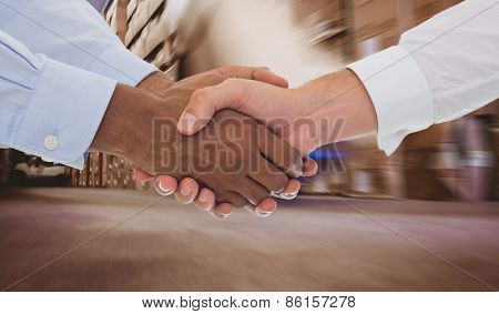 Close-up shot of a handshake in office against worker with fork pallet truck stacker in warehouse