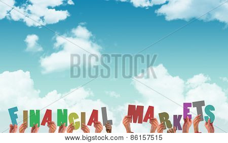 Hands holding up financial markets against blue sky