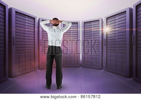 Businessman standing back to the camera with hands on head against server room with towers