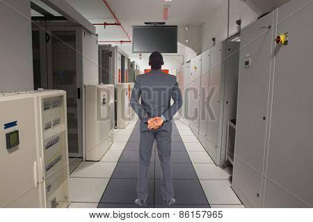Young businessman standing with hands behind back against data center