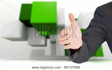 Businessman extending arm for handshake against green tile design
