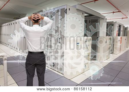 Businessman standing back to camera hands on head against data center