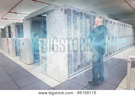Thoughtful businessman standing back to camera against data center