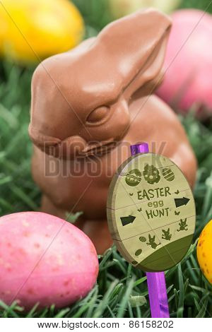 Easter egg hunt sign against colourful easter eggs with chocolate bunny