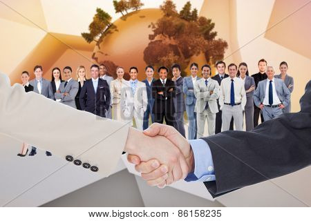 Smiling business people shaking hands while looking at the camera against globe on abstract background