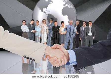 Smiling business people shaking hands while looking at the camera against planet on grey abstract background