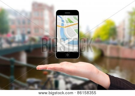 Hand showing map app on phone against canal in amsterdam