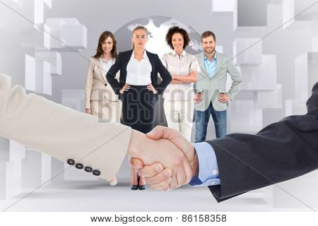 Smiling business people shaking hands while looking at the camera against planet on grey background with cubes