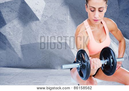 Strong woman doing bicep curl with large dumbbell against grey angular background