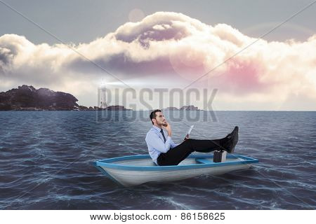 Businessman in boat with tablet pc against calm sea with lighthouse