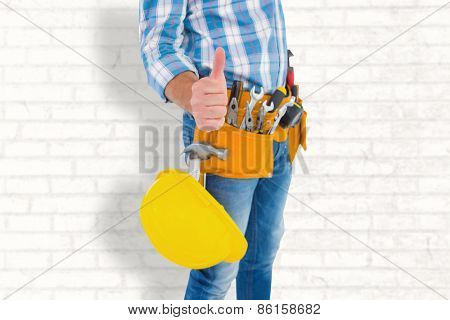 Midsection of manual worker gesturing thumbs up against white wall