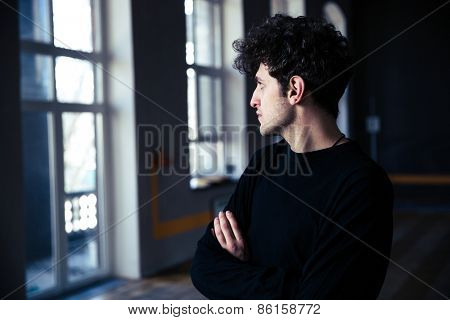 Handsome young man with curly hair standing with arms folded at gym