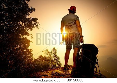 Backpacker standing on top of the mountain with bottle of water at sunrise