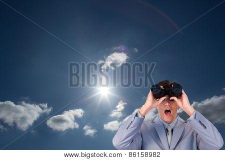 Suprised businessman looking through binoculars against sky
