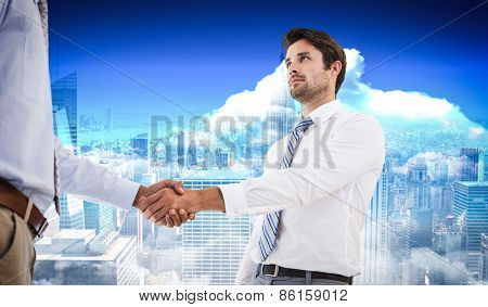 Two businessmen shaking hands in office against city skyline